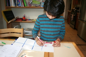 Boy 1 making a comic book